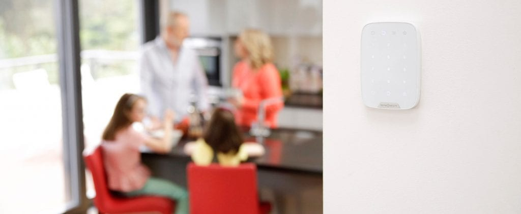 alarm system keypad on wall family in kitchen