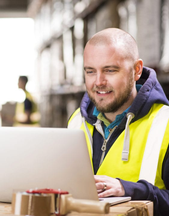 man in high vis on laptop
